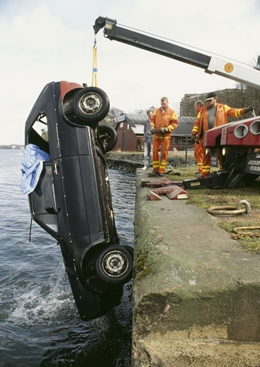 Emergency services lifting car from canal