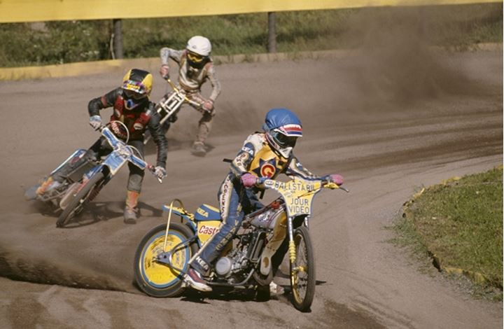 Motocross racers at a turn on the dusty road