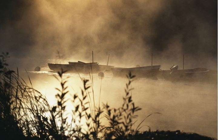Morning fog over river with moored boats
