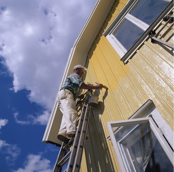 A man painting a yellow house. Sweden