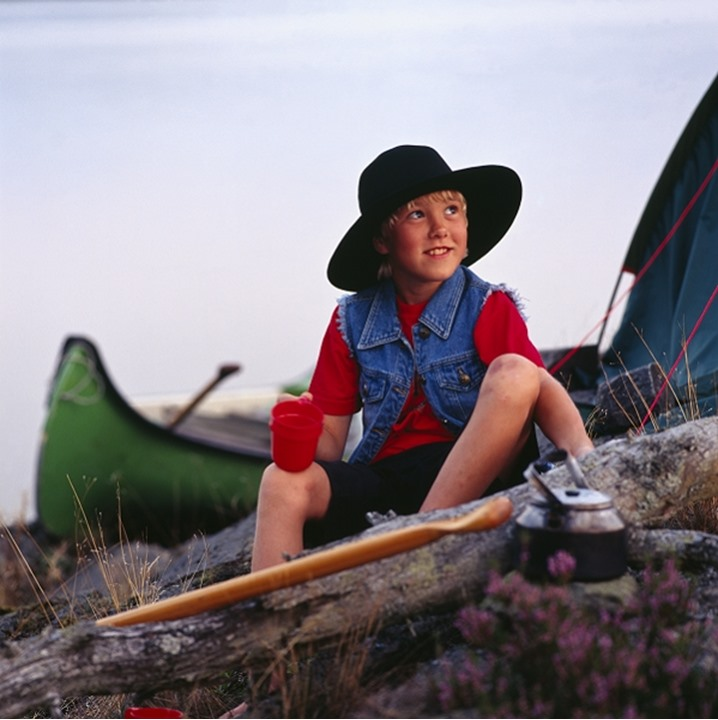 A boy with a hat at a camping trip. Sweden