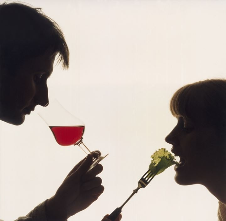 Close-up of a man drinking red wine and a woman eating salad with a fork