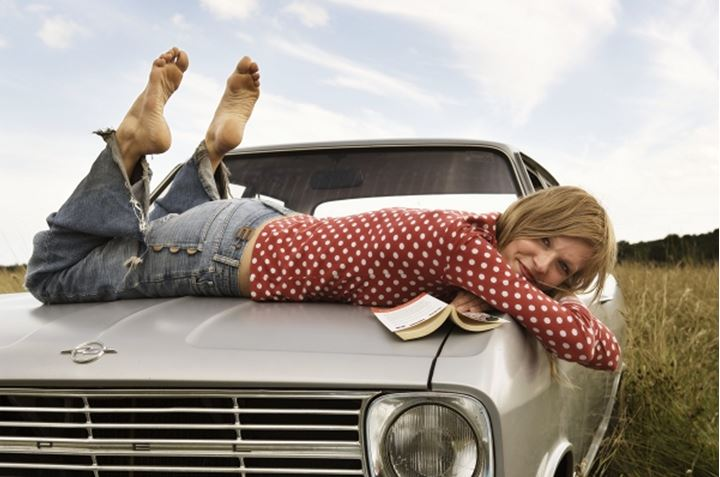 Woman laying on the hood of a car