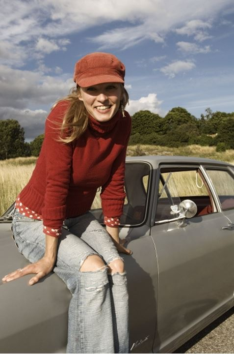 Smiling woman sitting on the hood of a car