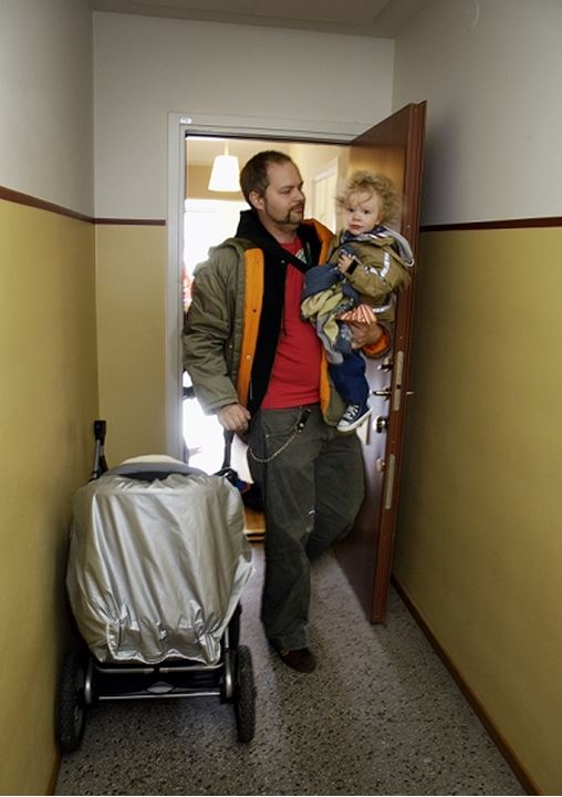 Father holding his daughter walking out of their apartment