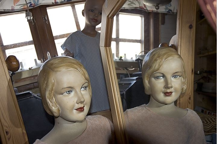 Two dolls by a mirror