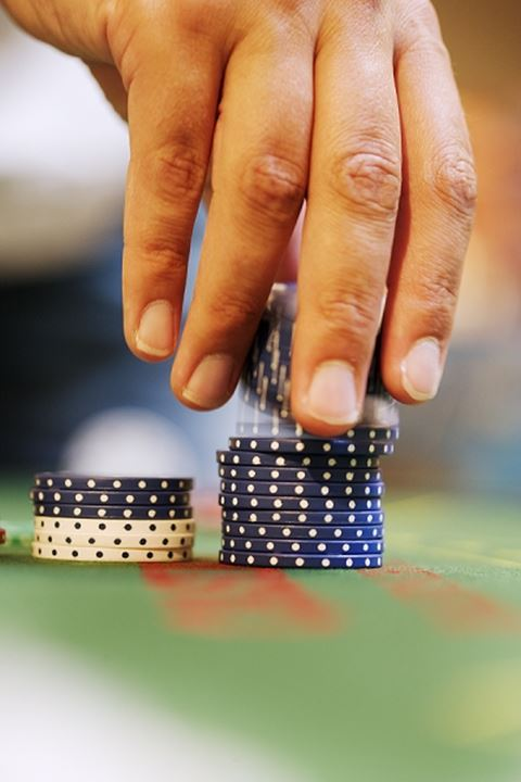 Close-up of a person's hand placing gambling chips on a roulette table.Malmo
