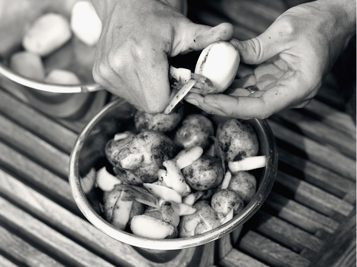 Hands of a man peeling potatoes