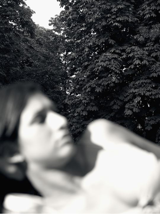 Trees behind a woman lying on the glade