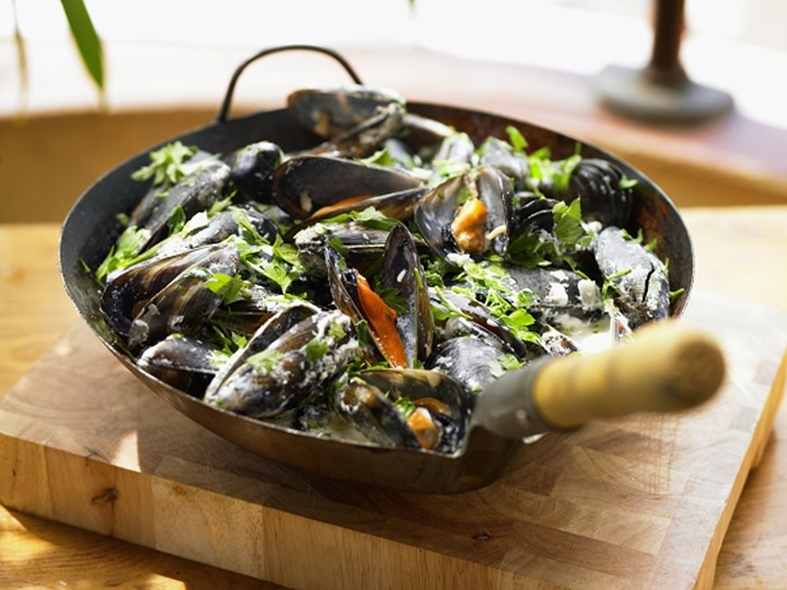 Mussels and vegetables in a frying pan