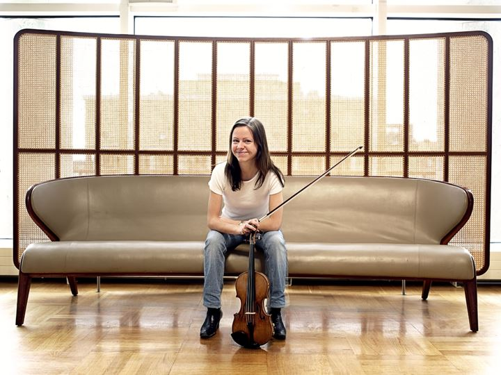 A smiling violinist sitting on a sofa