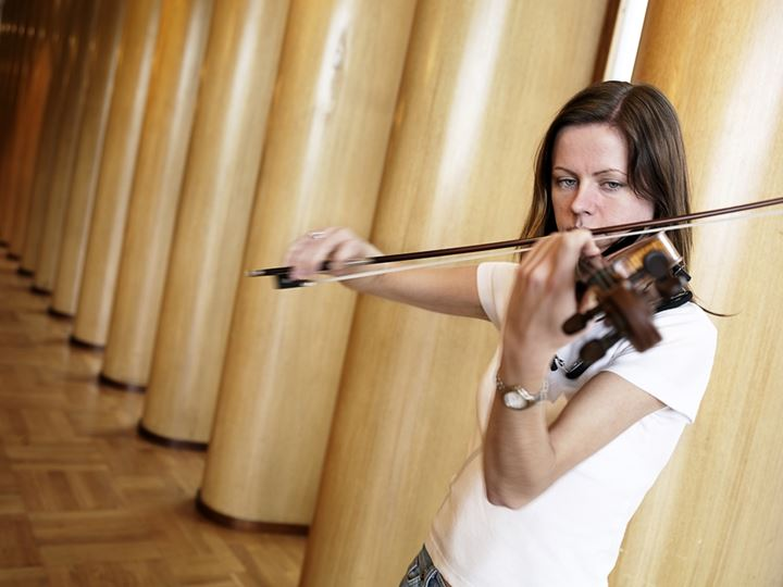 Woman playing violin standing by a row of columns