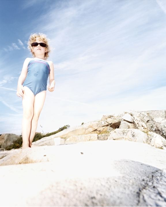 A girl wearing bathing suit and sunglasses standing on a stony hillock