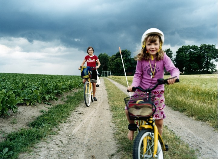 Girls cycling on a path in the countryside, Sweden