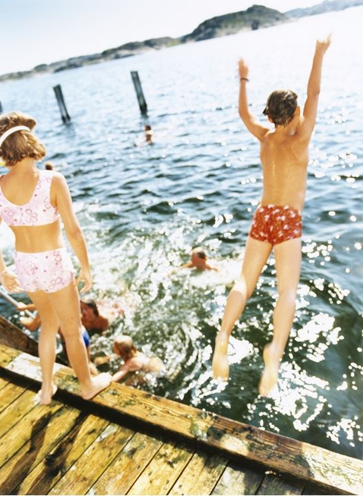 A boy jumping into the water, and a girl standing on the jumping-off place