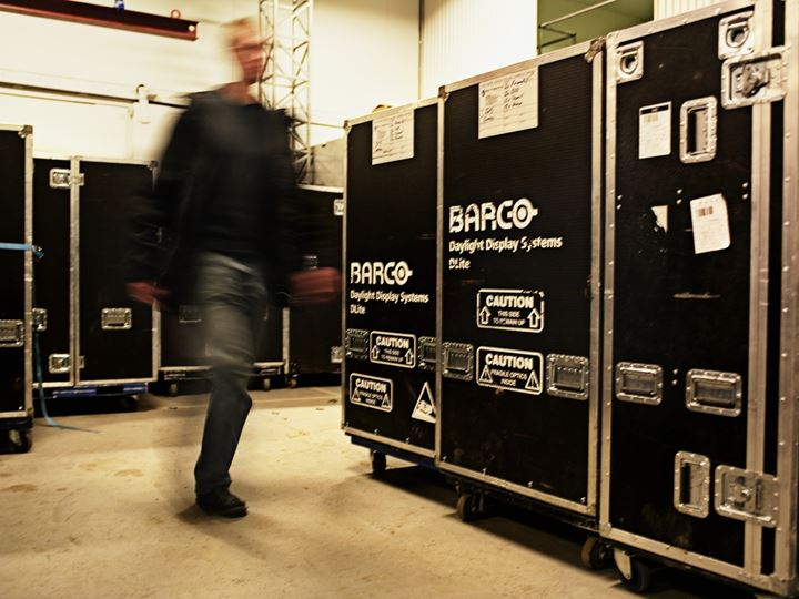 A man passing by boxes containing Barco equipment