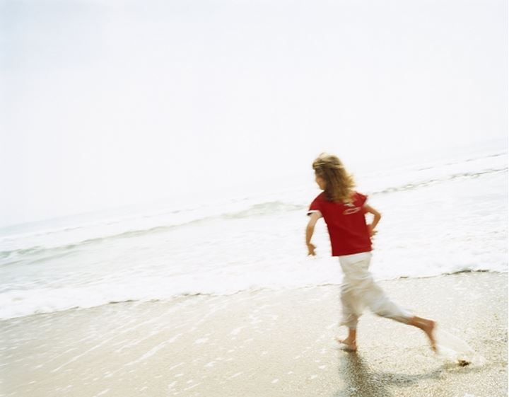 Girl running along a beach