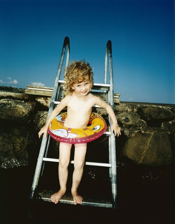 A little girl wearing an inflatable ring standing on a ladder leading to water
