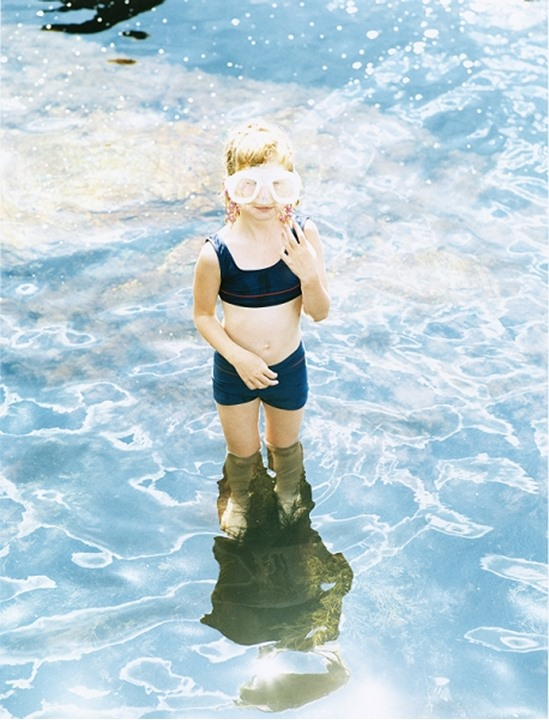 A young diver standing in knee-deep water