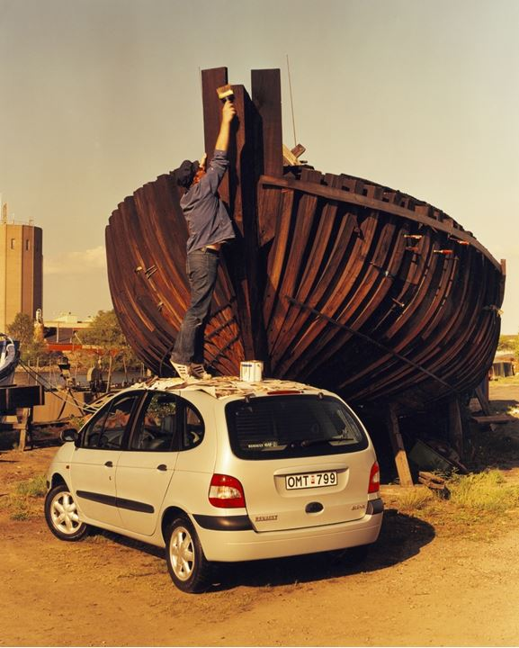 Man staining bottom of a boat out of roof of a car