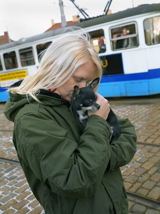 A girl and her pet at a tram station