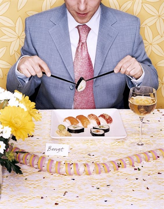 A man eating sushi with chopsticks, using them incorrectly