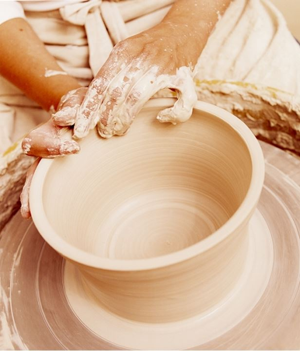Hands of a potter making an urn