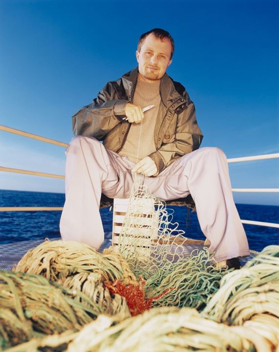 A fisherman sitting on the rostrum and repairing nets