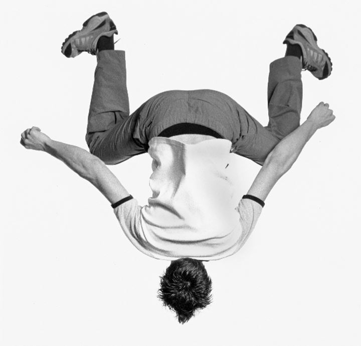 Rear view of a teenage boy jumping upside down in air