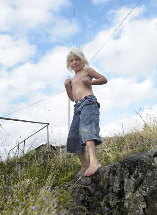 A half-naked boy standing on a hillside