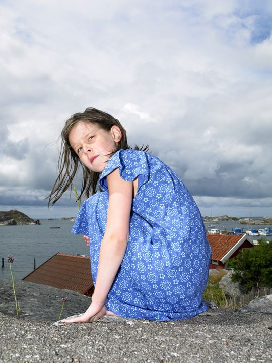A girl sitting on a hill against a bay