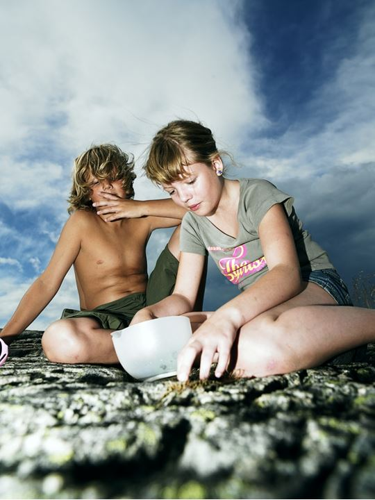 A girl and a boy sitting on a stony slope