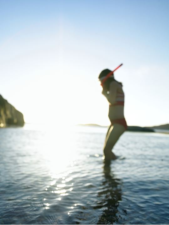 A girl with a snorkel, wading in the sea