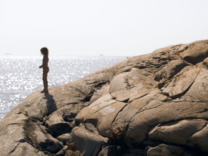 Side profile of a girl standing on the rock