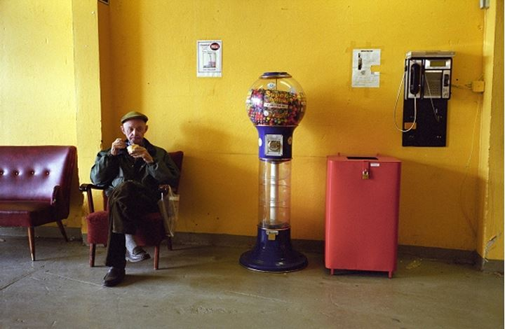 Old man sitting alone on a chair, eating an ice-cream at Kolaportid, Reykjavik's free market. Iceland.