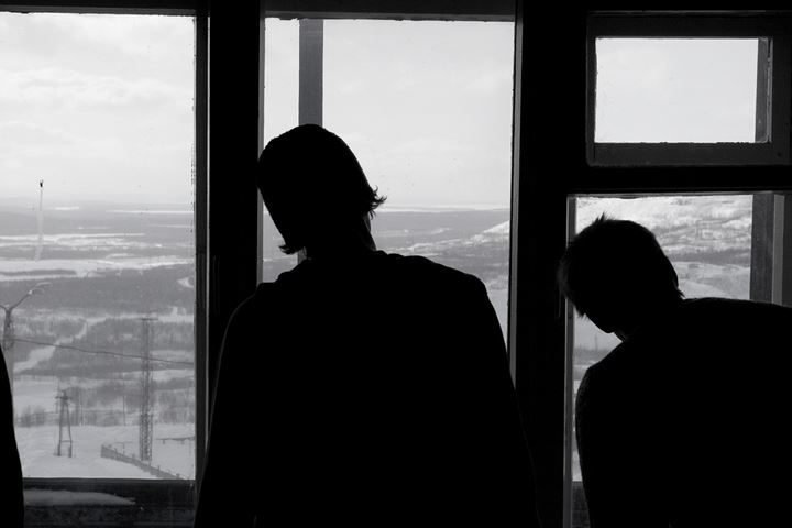 Two people locking out of a window