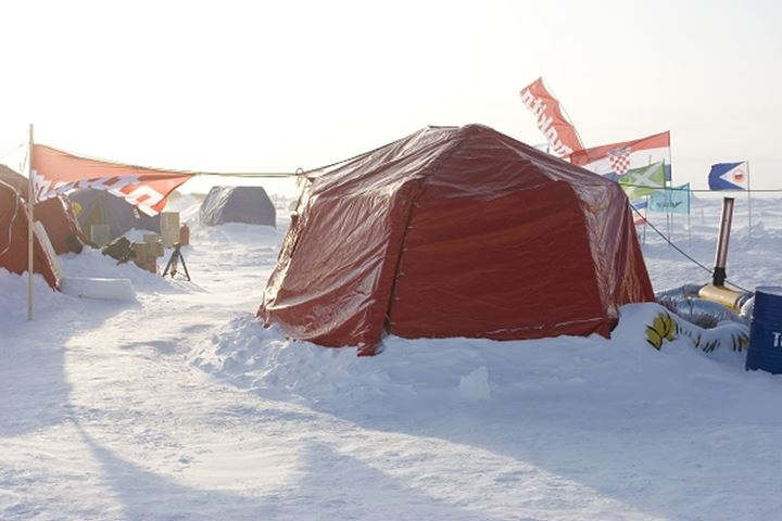 Tent with flags on snow in the North Pole