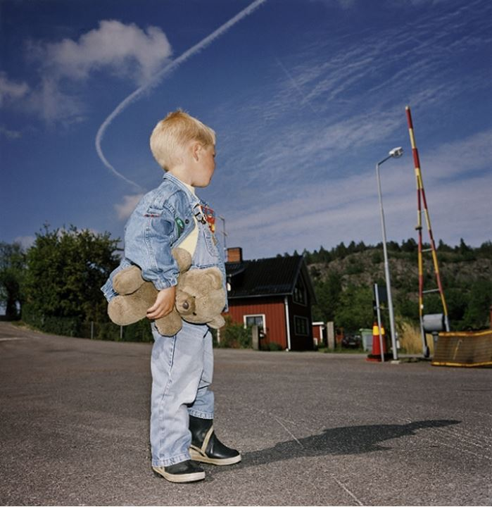 A boy with a teddy bear standing on a road