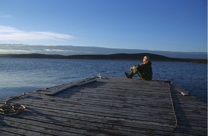 Side view of a man sitting on the dock near river