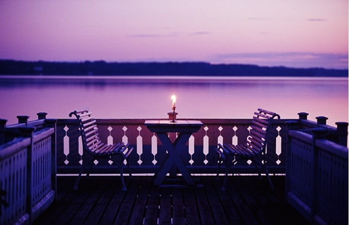A lit candle on a table on a veranda by a lake