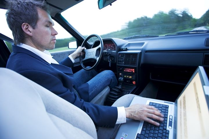 Man working with his laptop while driving