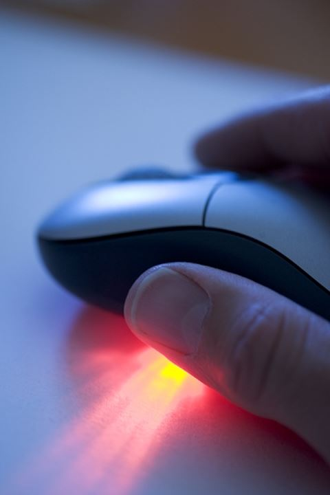 Fingers of a man on a computer mouse