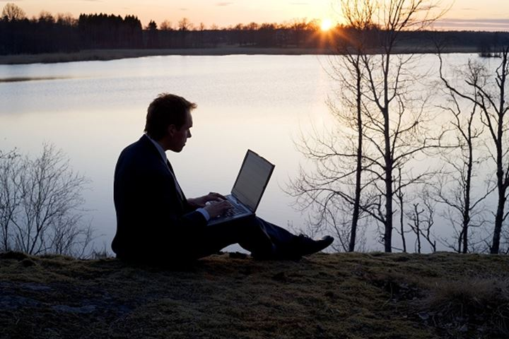 A man with his laptop sitting on a lakeside