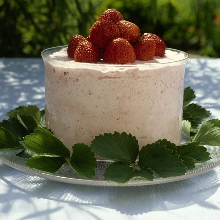 A bowl with cream and strawberries