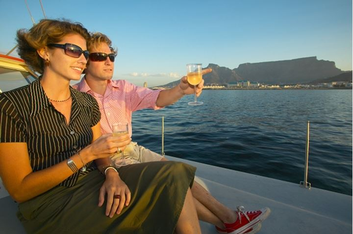 Couple on sunset cruise on a catamaran. Cape Town. Western Cape. South Africa