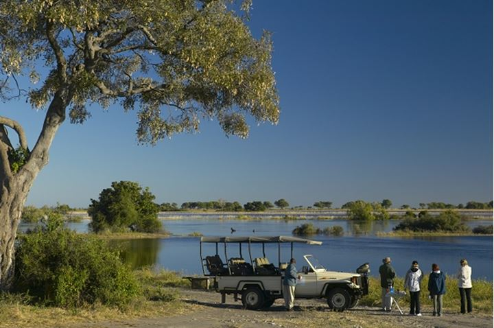 Tourists on game drive having a coffee break on the banks of the Chobe River. Chobe National Park. Botswana.
