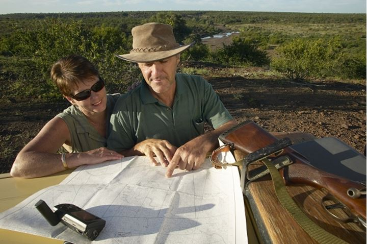 Explorers reading a map in the veld.  Mashatu Game Reserve. Northern Tuli Game Reserve. Botswana.