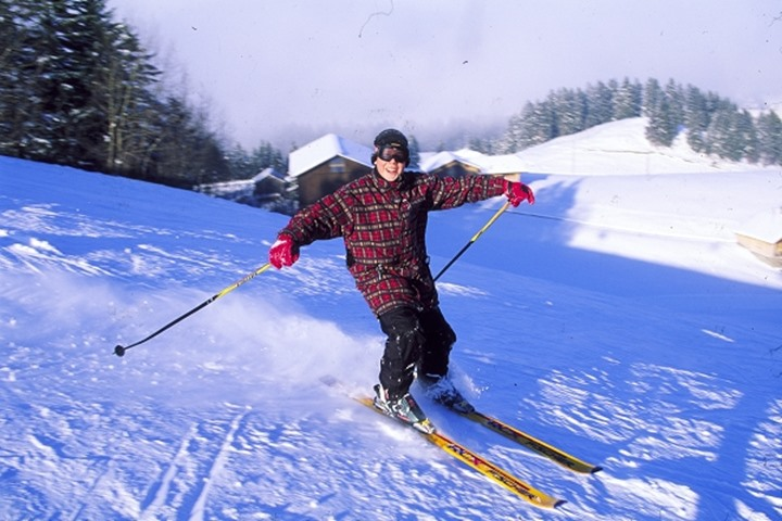 A boy downhill skiing