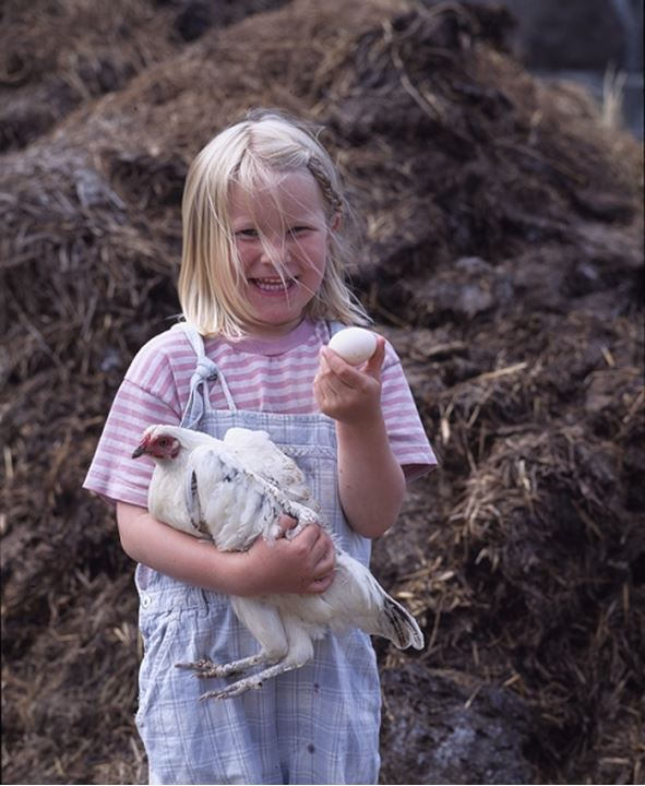 A girl holding hen and egg