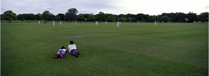 Two people lying watching a cricket game